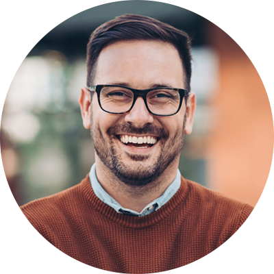 Smiling testimonial man with glasses and dark orange sweater.